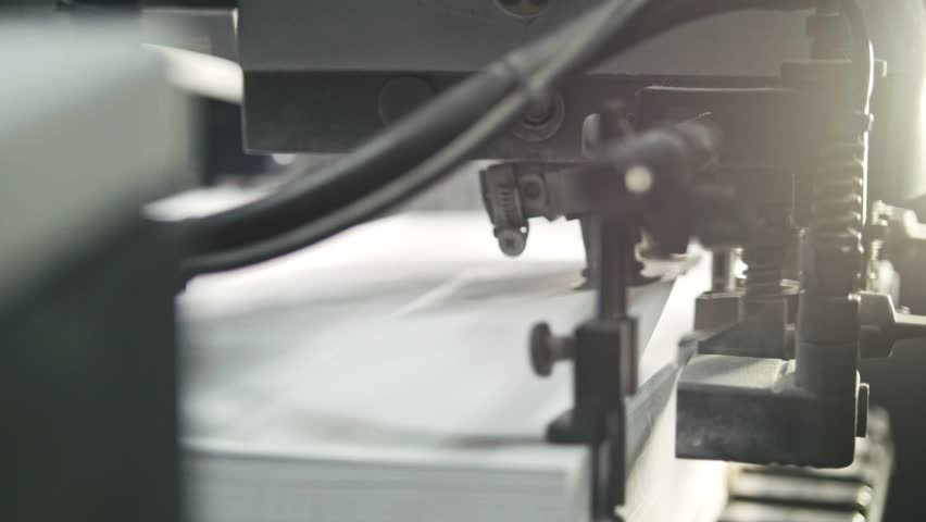 Printed sheets of paper are served in the printing press. Offset printing, CMYK, close up | Shutterstock HD Video #19782478