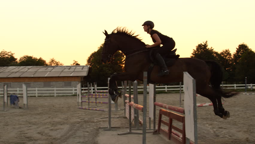 SLOW MOTION CLOSE UP: Young girl horseback riding strong brown horse jumping the fence in outdoors sandy parkour dressage arena at sunrise. Competitive rider training jumping over obstacles at sunset