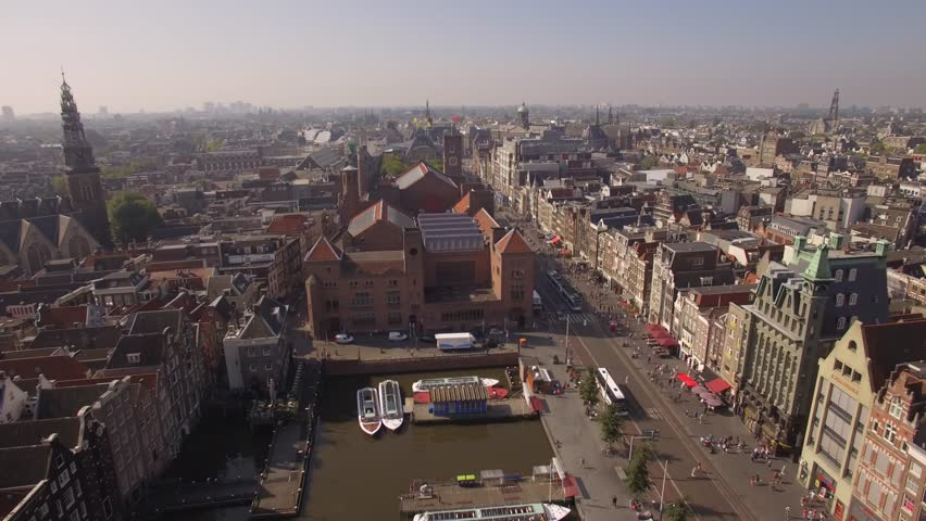 Amsterdam aerial sightseeing. Flying above old centre district. Netherlands in 4K.
