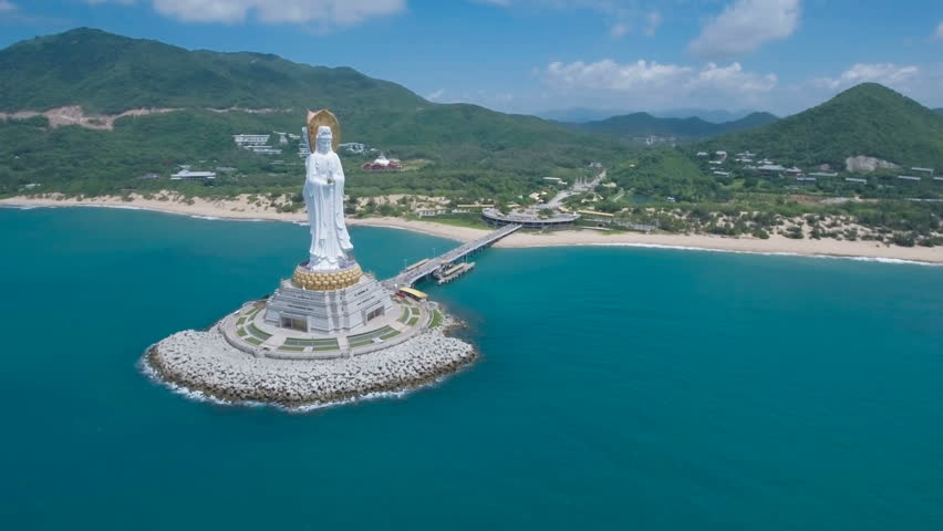 Flying towards a tall white Buddha statue on the tropical island Hainan, located in the South China Sea.
