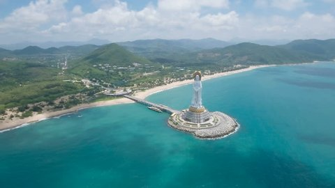 Aerial view of a tall white Buddha statue on Hainan island, perhaps symbolizing some of the territorial claims China makes in the region.