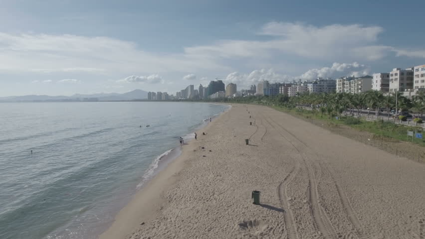 Aerial drone flight over the long beach in front of the skyline of Sanya, a medium sized city on the tropical holiday island of Hainan in the South China Sea.