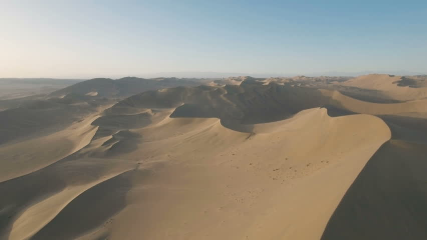 Flying towards huge sand dunes in the arid deserts around Dunhuang in China. Aerial view of dry rugged landscape.  #19847548