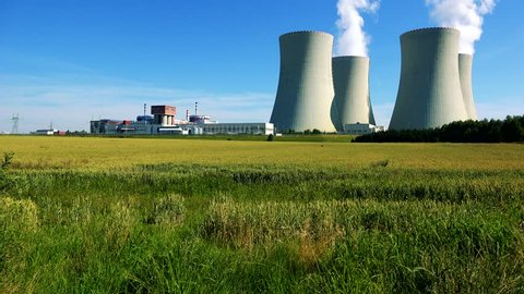 factory (nuclear power station) - closeup of buildings and smoke from chimney - field with plants and blue sky