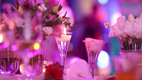 candles at the wedding table, blurred silhouettes of people dancing in a disco, banquet, decoration, restaurant, close-up