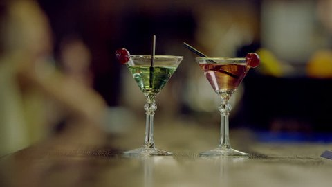 two martini glasses on a bar counter
