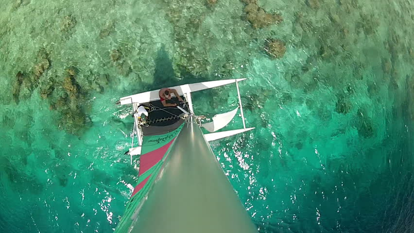 catamaran sailing in lagoon near coral reef, top view