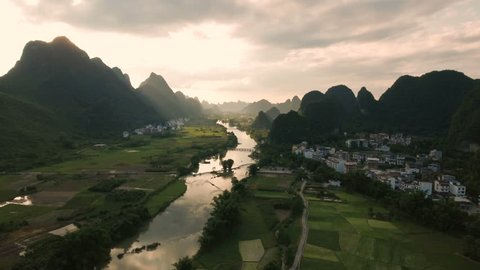 Peaceful idyllic aerial scene of a beautiful rural region in China. Flying over green rice fields, among limestone karst scenery, towards a setting sun.