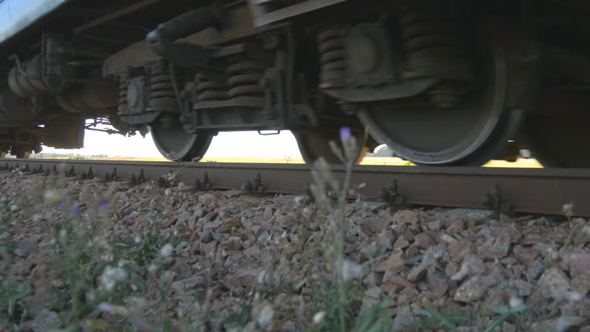 Passenger train passes by a camera. Wheels of the train moving along the rails closeup. Close-up shot of a passenger train passing by. Comfortable traveling by train.