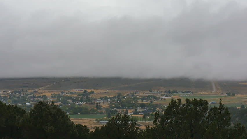 SANPETE COUNTY, UTAH - SEPTEMBER 2016: Time lapse-Low cloud layer moving over rural mountain valley farming community on rainy overcast autumn day. Viewed down from high tree-covered mountain ridge.