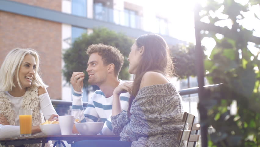 Young beautiful people talking, drinking and enjoying sunny weather while sitting at the table and having picnic outdoors. Group of friends enjoying meal at outdoor party in back yard. | Shutterstock HD Video #20018095