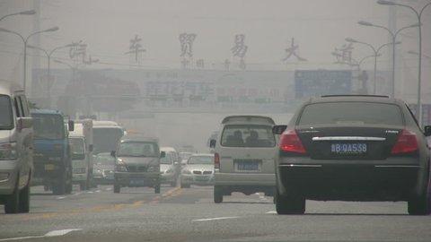 QINGDAO - APRIL 29: Traffic drives through thick smog at a road on April 29, 2010 in Qingdao, China.