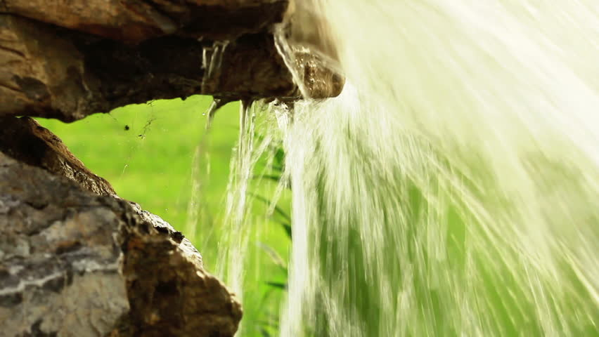 Water bursting out of stone spring in nature