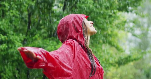 happiness and rain. A happy woman smiles in the rain, the woman immersed in the nature of dance under the rain in slow motion. Concept of love, nature, happiness, freedom.