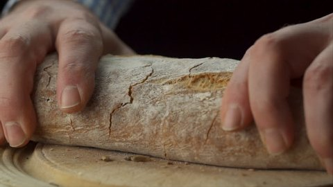 static view of mans hands tearing loaf of bread in half