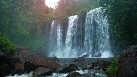 Wide curtain of whitewater flows continuously over the brink of a beautiful. natural waterfall in Cambodia. with sound.