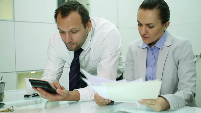 Business couple making calculations using a calculator   | Shutterstock HD Video #2010368