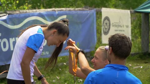 TUNGUR, RUSSIA - 07.2016: award ceremony of ALTAY ULTRA TRAIL.Young beautiful girl is awarded a gold medal for the first place.