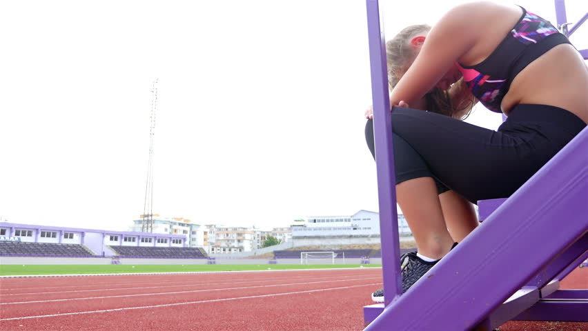 Teenager girl athlete taking breath tired exhausted disappointed after running on a stadium #20124190