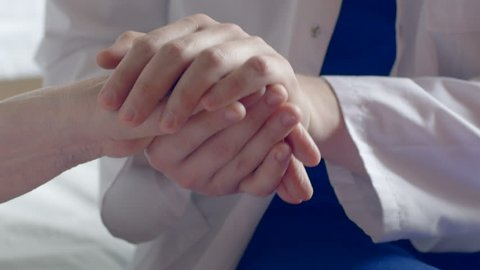 Close-up of a doctor holding a wrinkled hand at the hospital. Man wearing a white coat comforting a weak old patient.