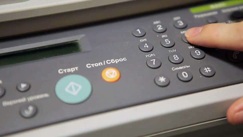 Human Caucasian hands pushing buttons on fax machine