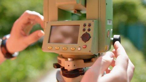 Surveyor at work measuring the distance. One caucasian man in orange vest. Closeup shot.