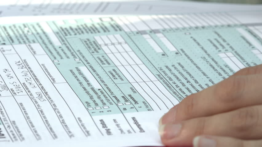 Fill in the form for taxes: US taxes, tax return, young woman | Shutterstock HD Video #20158708