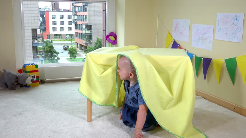 Child hiding under table covered with plaid