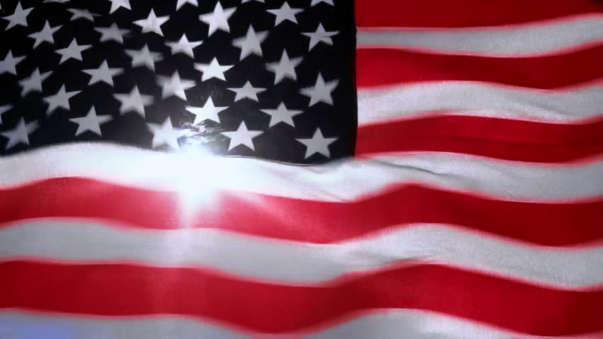 American flag through which the sun shines and it is flying in the wind | Shutterstock HD Video #20182198