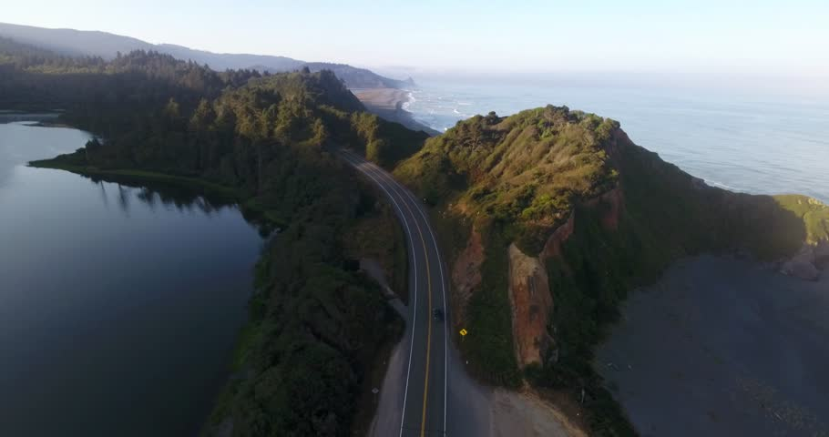 Aerial shot of a car driving on a State Route 1 - the Pacific Coast Highway in California, USA