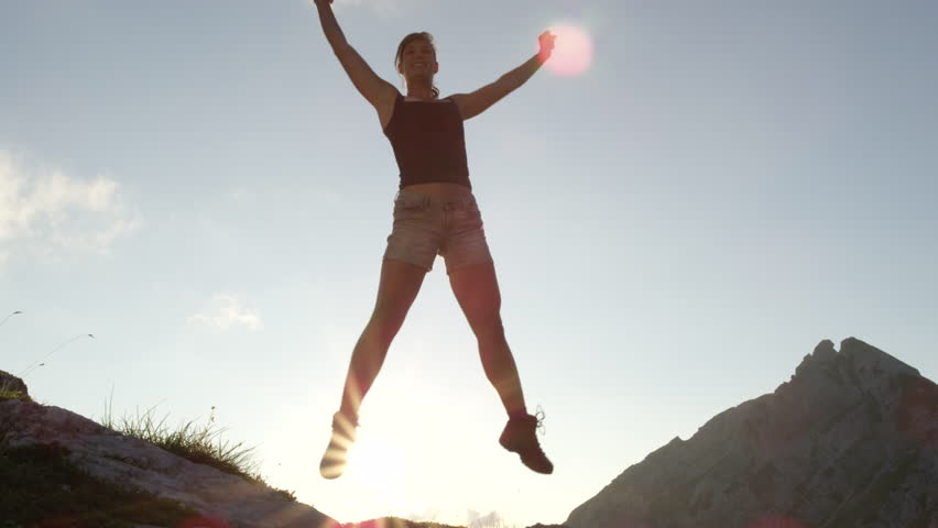 SLOW MOTION, CLOSE UP, LOW ANGLE: Cheerful young woman standing on big rock on mountain peak, raising her hands up, jumping and outstretching legs on amazing sunny evening. Happy girl enjoying success