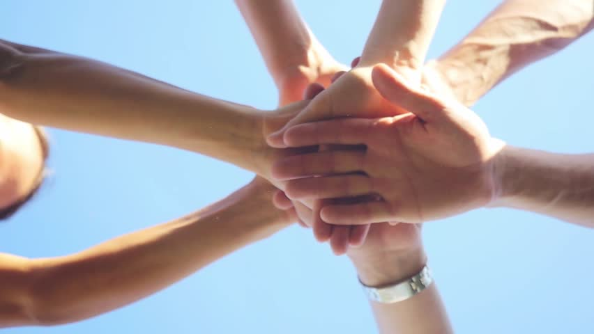 Successful team: many hands holding together on sky background in slowmotion. 1920x1080