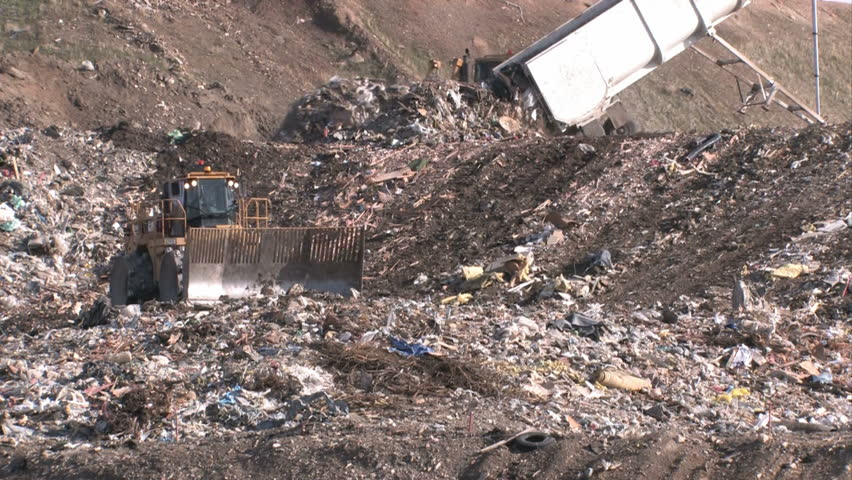 Garbage dump in Utah. Bull dozers moving garbage and trash around. A mountain of a landfill. Pollution and debris from business and residence household waste. Environmental waste non biodegradable.