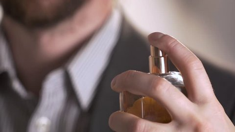 close up of handsome young business man using perfume