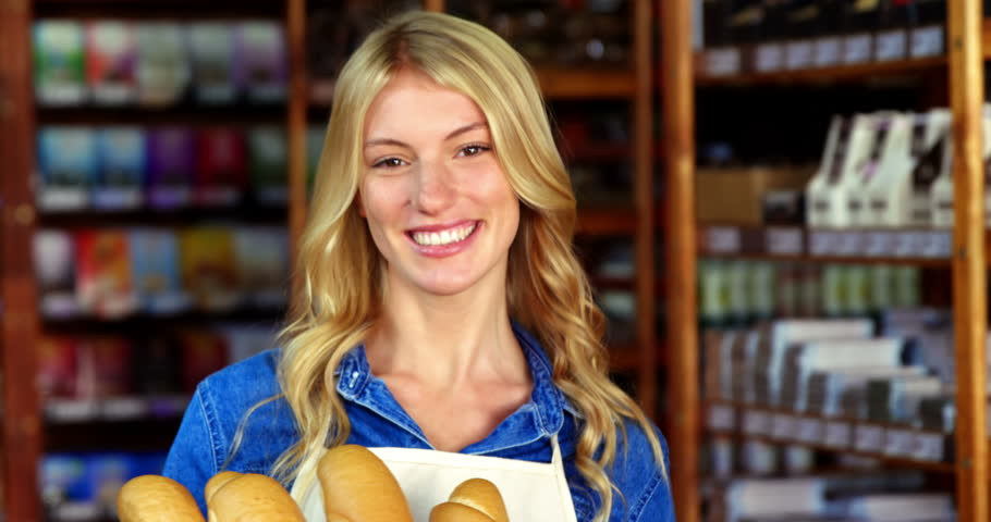 Smiling woman holding a basket of baguettes in organic shop of supermarket 4k | Shutterstock HD Video #20300905