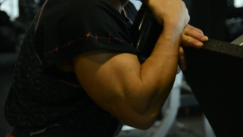 Muscular athlete drinks water from a black plastic bottle. The man in gym
