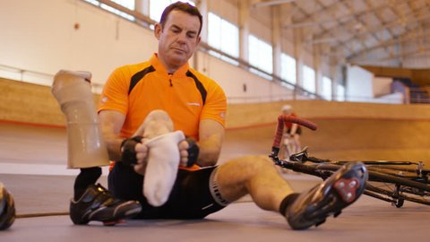 4K Man with prosthetic leg at cycling track attaches his limb and prepares for a training session. Shot on RED Epic.