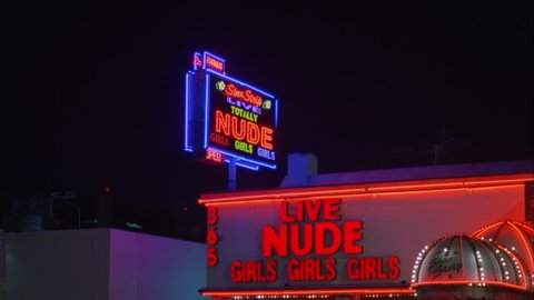 night , up angle, neon Live Nude Girls Girls sign, then tilt down right brick stone strip club nude bar awning, twinkle lights two Greek Roman style nude women statues pedestals