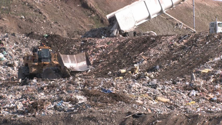 Garbage dump Utah. Bull dozers and large dump truck unloading and moving garbage and trash around. Pollution and debris from business residence household waste. Environmental waste non biodegradable.