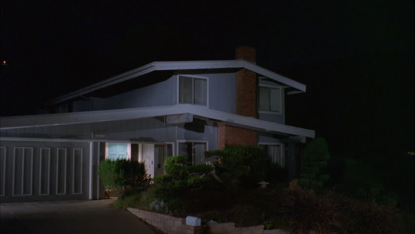 night typical 1970s style light blue gray slat wood two story house hills, brick chimney, only porch light on, then see right corner upstairs window light turn on, Left,