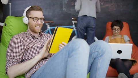4K Businessman making video call on computer in trendy creative office. Young fun startup company. Shot on RED Epic.