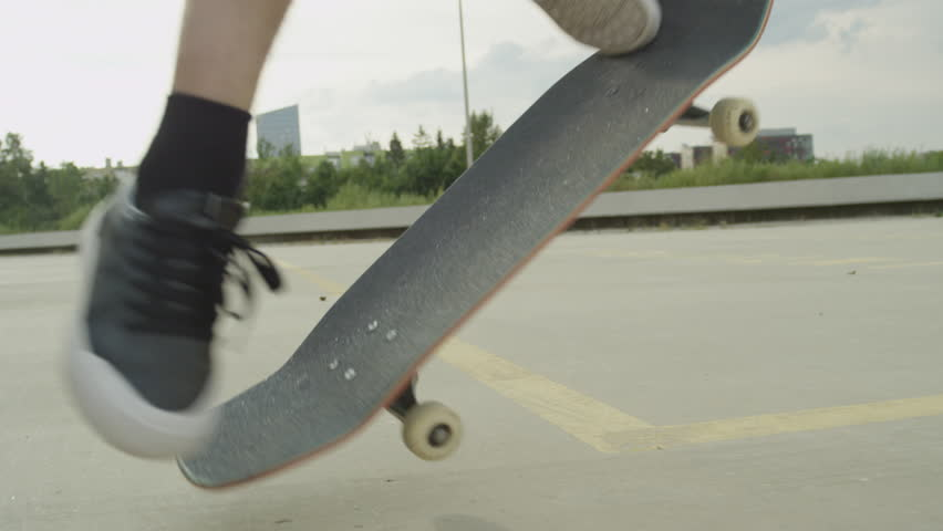 SLOW MOTION CLOSE UP: Unrecognizable skateboarder skateboarding and jumping flip ollie trick on concrete street. Extreme closeup of skateboarder's legs jumping flip trick with skateboard in the city
