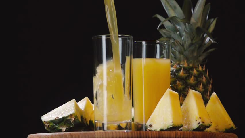 Pouring pineapple juice into glass slow motion HD video. Still life fruits composition isolated on black background