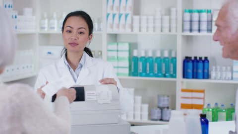 4K Friendly pharmacy worker giving prescription order to senior lady. Shot on RED Epic.