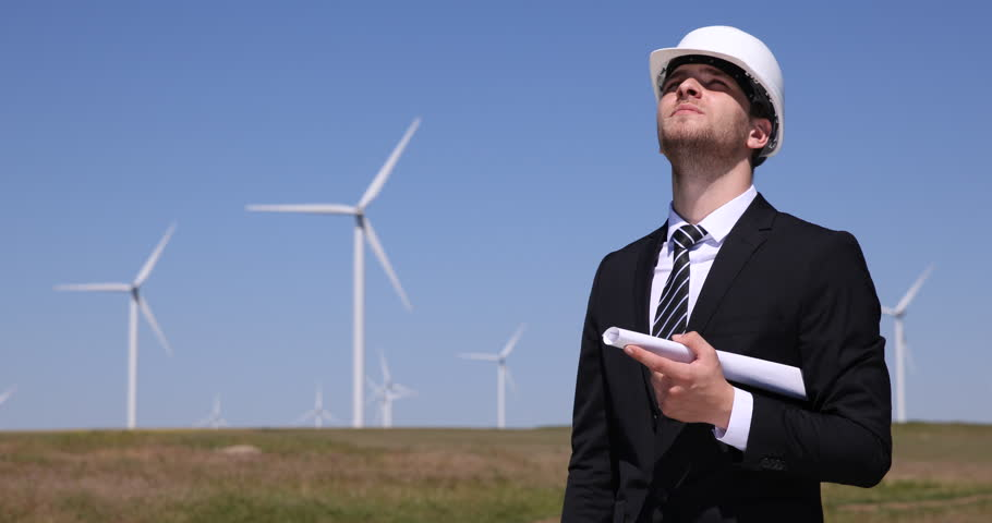 Engineer man looking at wind turbines and blueprint analyzing power businessman planning reading wind turbine blueprint clean electricity production ultra high definition ultrahd malvernweather Choice Image