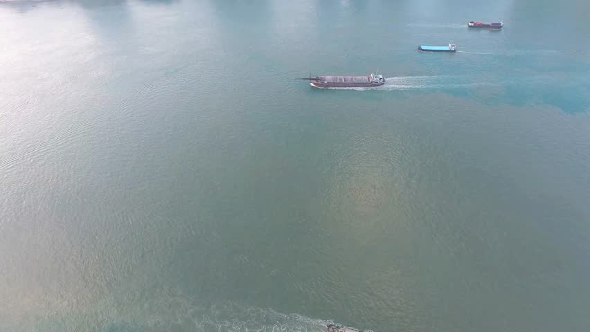 An aerial view fly over barge transporting dredged sand on the sea