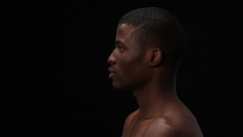 Close up profile of naked black man posing in studio. Handsome model man posing over black background. Man smiling for camera and touching his face. Fashion or vogue concept.