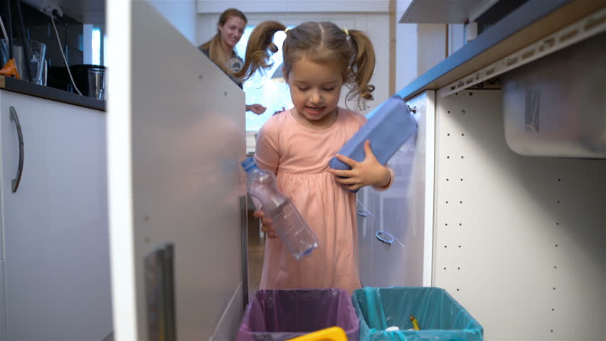 Little girl drops the trash into kitchen recycling bin.