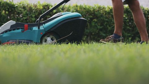 Man cutting lawn with grass mower