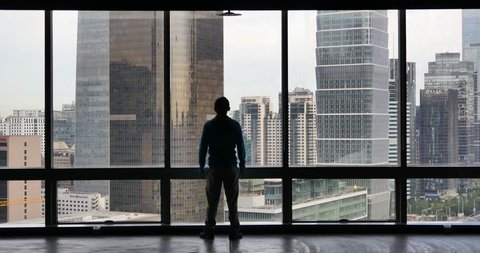 4k,a businessman Overlooking the urban business building from window,skyscrapers,economic center. gh2_11561_4k
